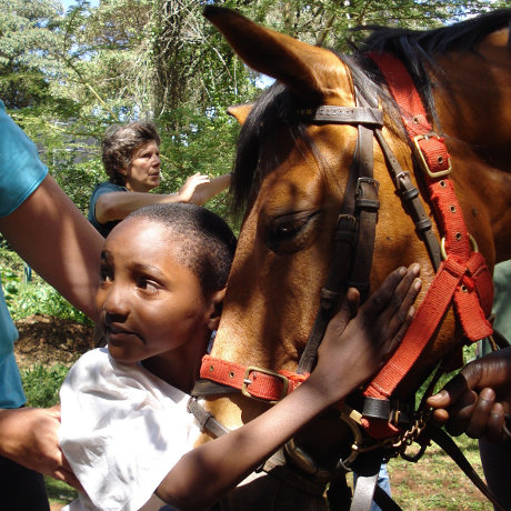 Child being helped into the saddle by volunteers